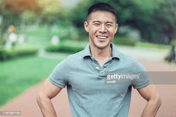 ritratto di uomo sorridente nel parco - polo foto e immagini stock