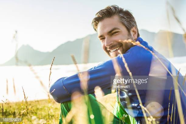 portrait of a smiling man sitting on a meadow in the mountains at dawn, achenkirch, austria - turning stock pictures, royalty-free photos & images