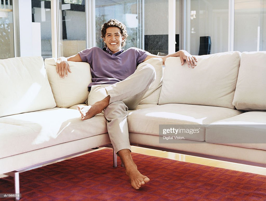 Portrait of a Smiling Man Sitting on a Sofa : Stock Photo