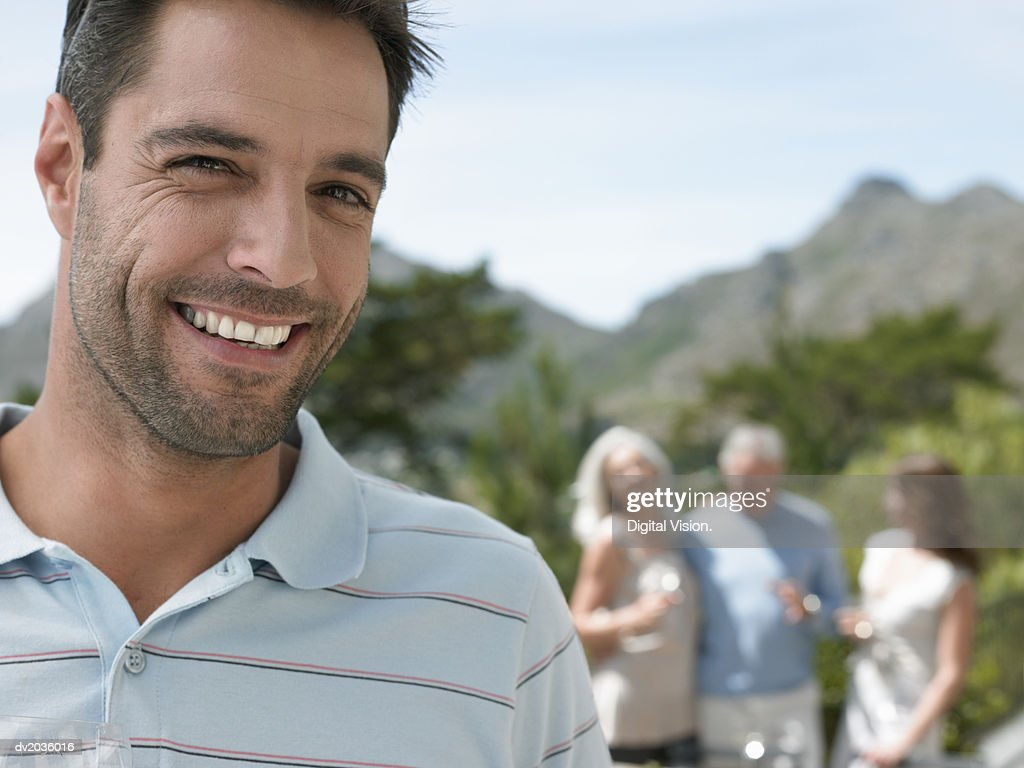 Portrait of a Smiling Man Standing in Front of People at a Garden Party : Stock Photo