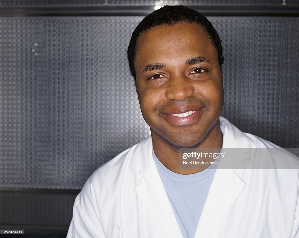 Portrait of a Smiling Man Wearing a Lab Coat Against a Grey Metallic Background : Stock Photo