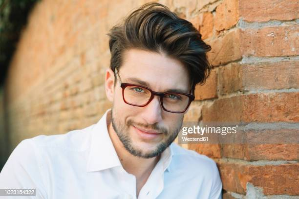 portrait of a smiling man wearing glasses at brick wall - mid adult men stock pictures, royalty-free photos & images