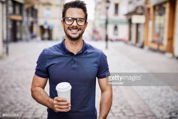 portrait of a smiling man with glasses holding coffee outdoors - cogiendo fotografías e imágenes de stock