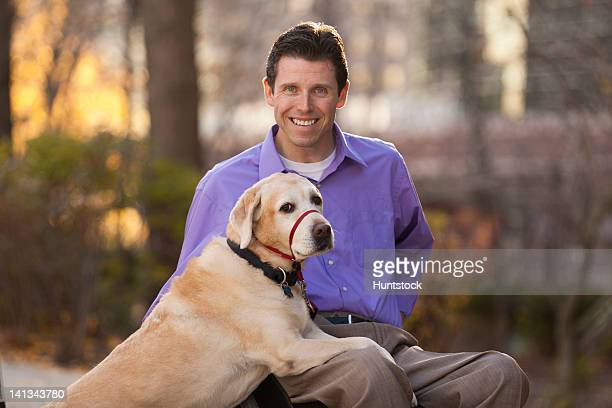 Portrait of a smiling man with spinal cord injury in wheelchair with his service dog