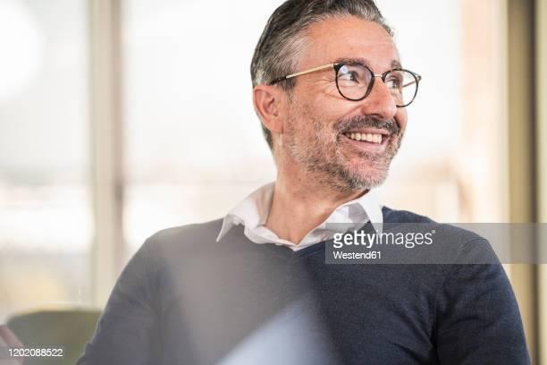 portrait of a smiling mature businessman in office looking sideways - 50 54 jahre stock-fotos und bilder