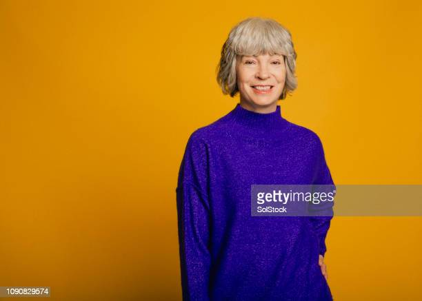 portrait of a smiling mature woman - colored background stock pictures, royalty-free photos & images