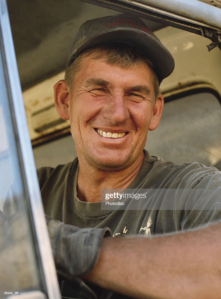 portrait of a smiling middle-aged caucasian farmer taken while he is sitting in his truck : Foto de stock