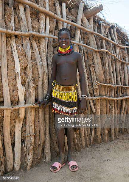 Portrait of a smiling nyangatom tribe girl with traditional beaded skirt omo valley kangate Ethiopia on March 15 2016 in Kangate Ethiopia