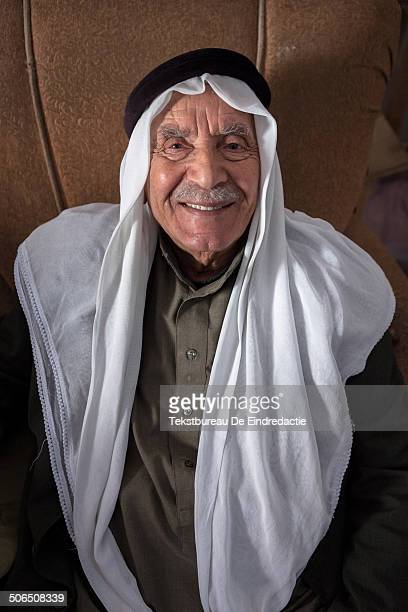 CONTENT] Portrait of a smiling old Palestinian man wearing a traditional Arab headscarf sitting in a leather chair running a shop in Madaba...