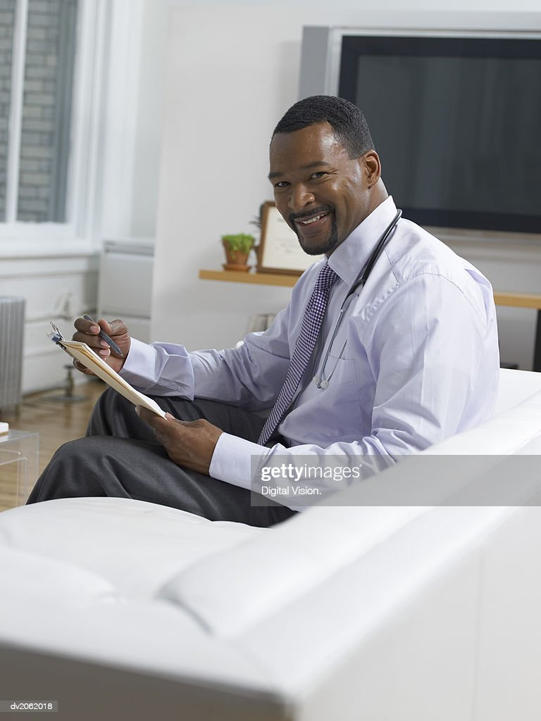 Portrait of a Smiling Physician Sitting on a Sofa and Holding a Clipboard : Stock Photo