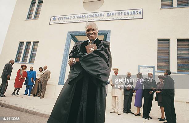 Portrait of a Smiling Priest Standing Outside a Church in Front of a Large Group of People