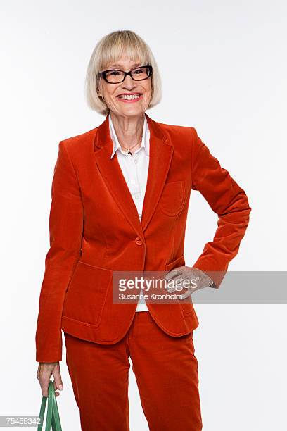 Portrait of a smiling Scandinavian elderly woman in a red suit.