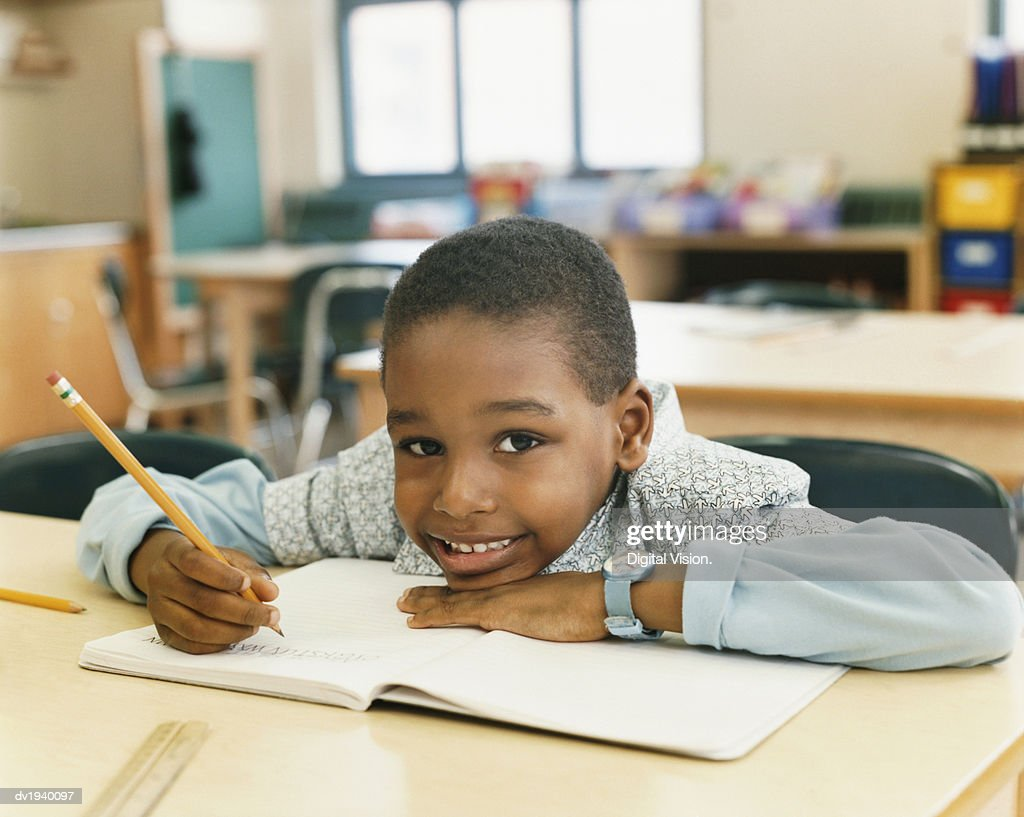Portrait of a Smiling Schoolboy Sitting at a Table and Resting His Head on a Exercise Book : Stock Photo