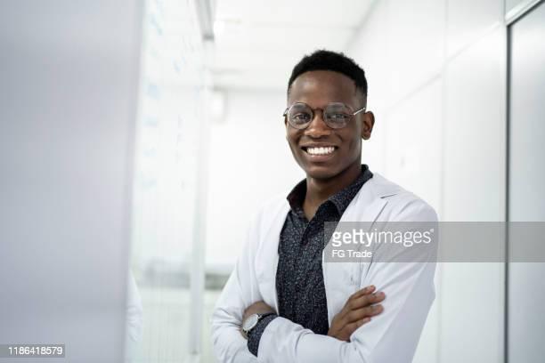 verticale d'un scientifique de sourire au laboratoire - blouse photos et images de collection