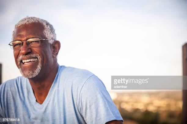 portrait of a smiling senior black man - black people laughing stock photos and pictures