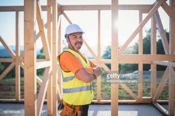 portrait of a smiling senior builder at the construction site. - working seniors stock pictures, royalty-free photos & images