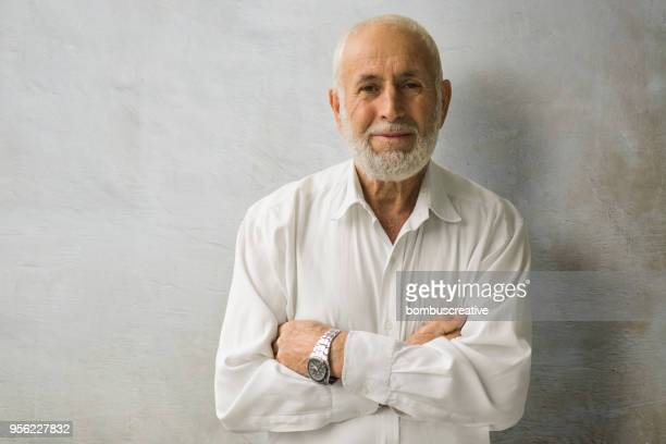 portrait of a smiling senior business man - middle east stock pictures, royalty-free photos & images