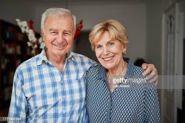 portrait of a smiling senior couple at home - cadrage à la taille photos et images de collection