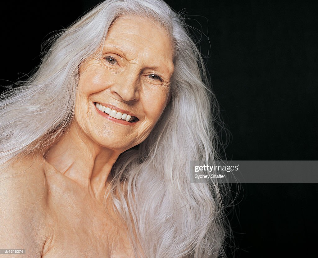 portrait of a smiling senior female nude with long grey hair stock