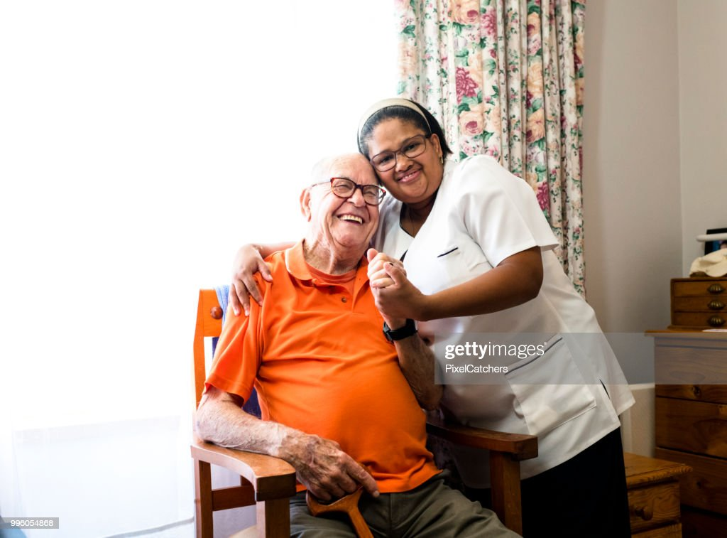Portrait of a smiling senior man and nurse embracing : Stock Photo
