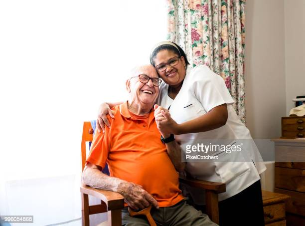 portrait of a smiling senior man and nurse embracing - outpatient care stock pictures, royalty-free photos & images