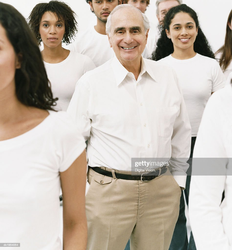 Portrait of a Smiling Senior Man in a White Shirt Standing in a Crowd : Stock Photo