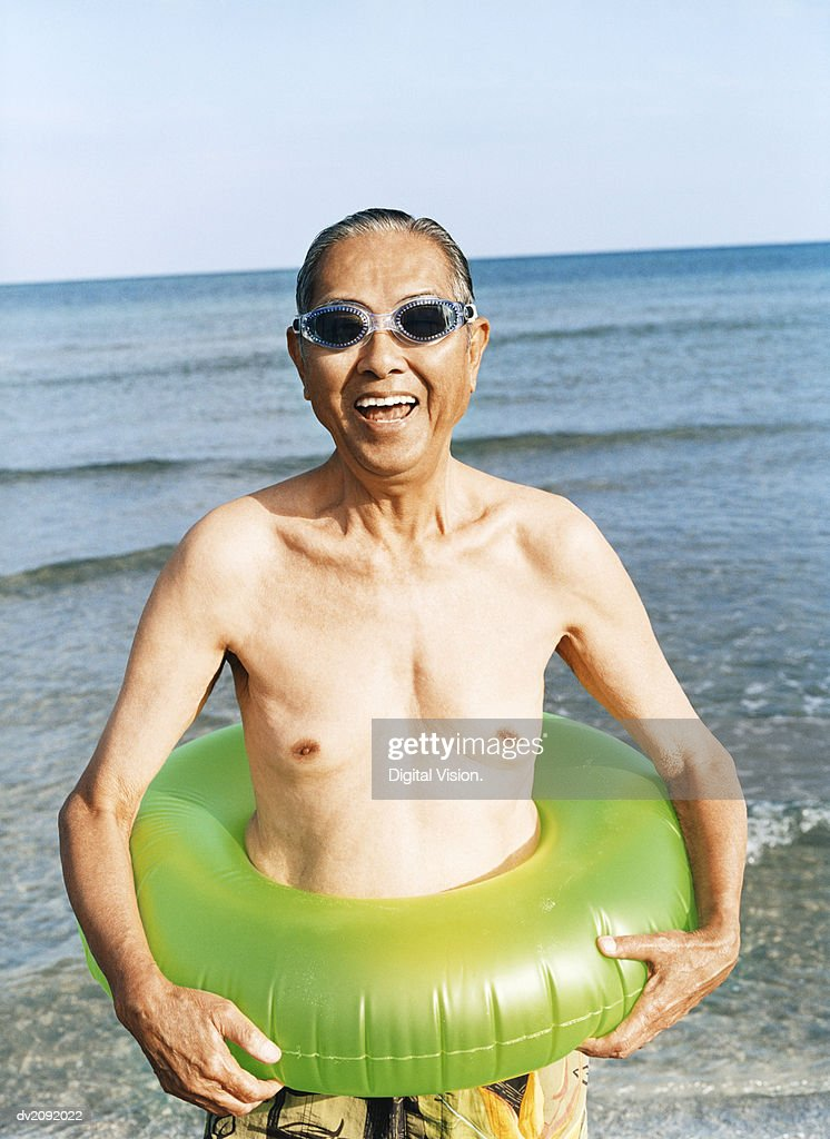 Portrait of a Smiling Senior Man Standing by the Sea, Wearing a Rubber Ring and Swimming Goggles : Stock Photo