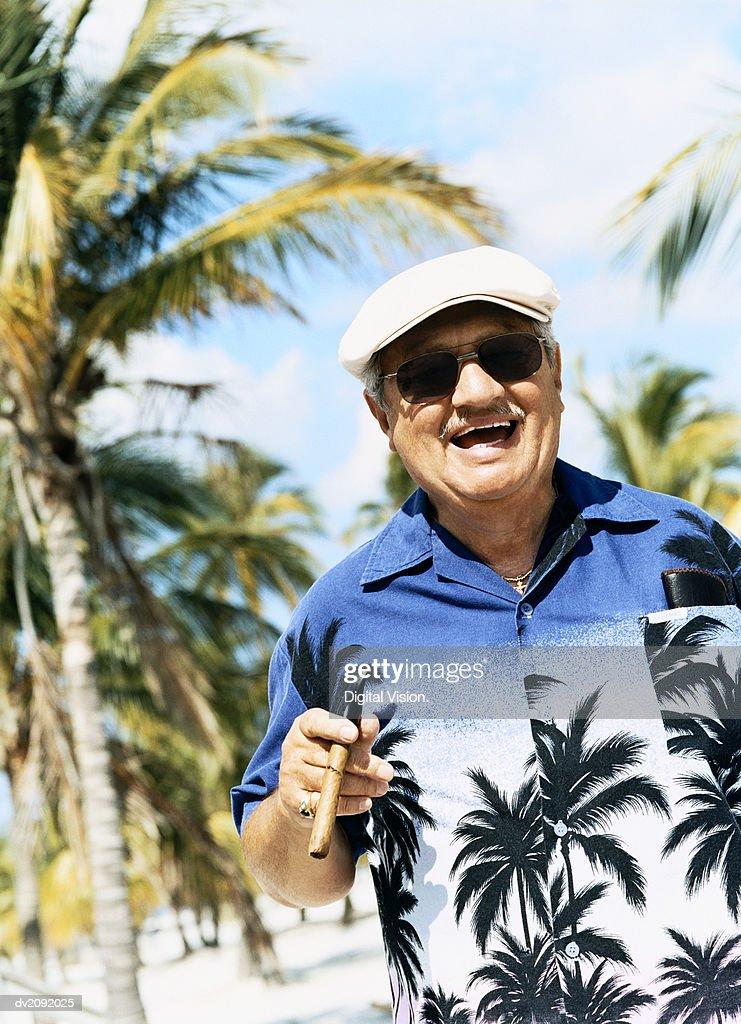 Portrait of a Smiling Senior Man Wearing a Hawaiian Shirt and Smoking a Cigar : Stock Photo