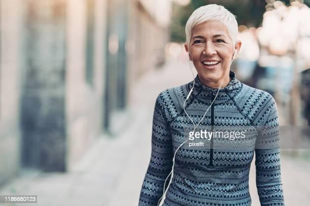 portret van een lachende senior sportvrouw - 55 59 jaar stockfoto's en -beelden