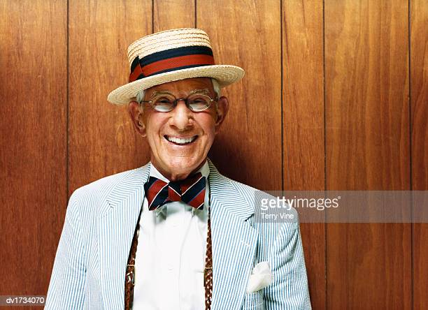 portrait of a smiling senior wearing a striped suit and a straw hat - revers stock-fotos und bilder
