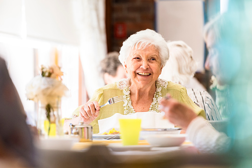 Portrait of a smiling senior woman having lunch with friends 985859318