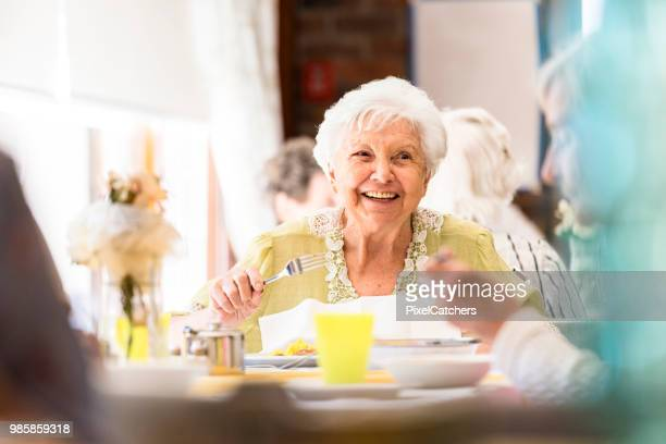 portrait of a smiling senior woman having lunch with friends - almoço imagens e fotografias de stock