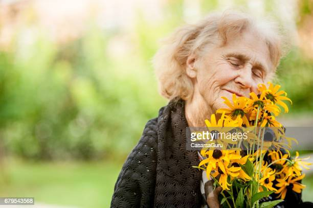 portrait of a smiling senior woman holding flowers - ricordi foto e immagini stock
