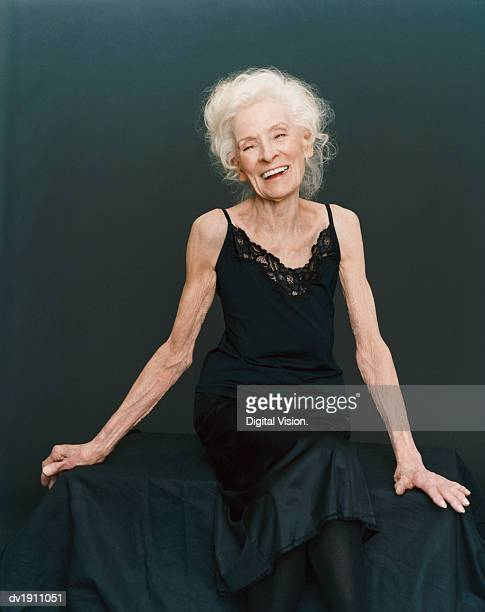 portrait of a smiling, senior woman sitting in an evening gown against a black background - grey dress stock pictures, royalty-free photos & images