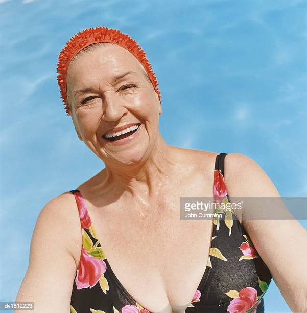Portrait of a Smiling Senior Woman Wearing a Red Swimming Cap