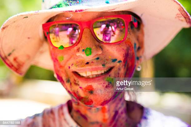 Portrait of a smiling senior woman with hat and mirror sunglasses covered with colorful Gulal powder during a Holi party to give welcome to the springtime during a sunday family reunion.