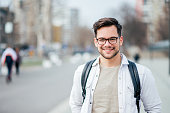 Portrait of a smiling student at the city street.