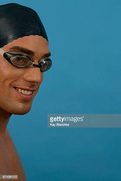 Portrait of a smiling swimmer wearing a bathing cap and goggles