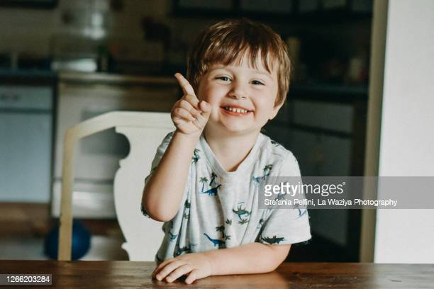 portrait of a smiling toddler while raising his index finger - esprimere a gesti foto e immagini stock