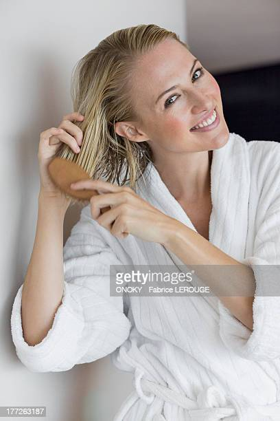 Portrait of a smiling woman brushing her hair