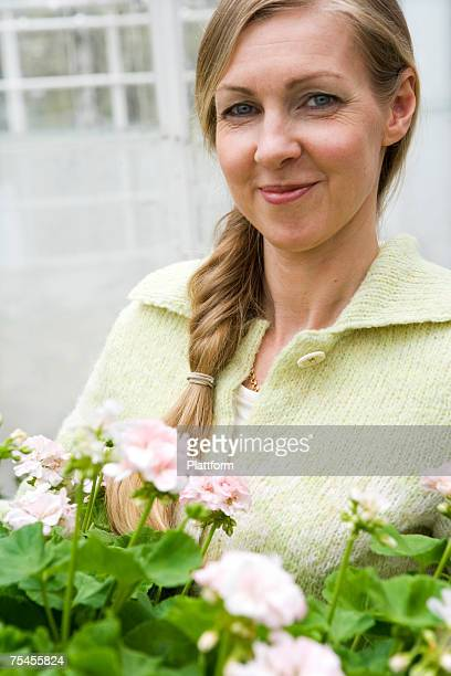 Portrait of a smiling woman carrying flowers.