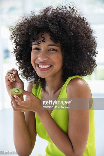 portrait of a smiling woman eating kiwi fruit with a spoon - kiwi fruit stock pictures, royalty-free photos & images