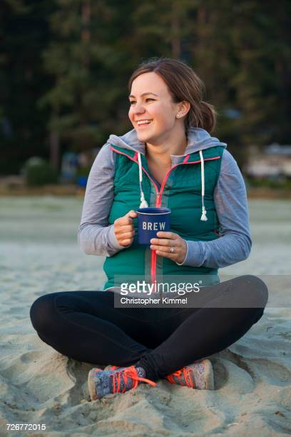 Portrait Of A Smiling Woman Enjoying Hot Drink At A Beach