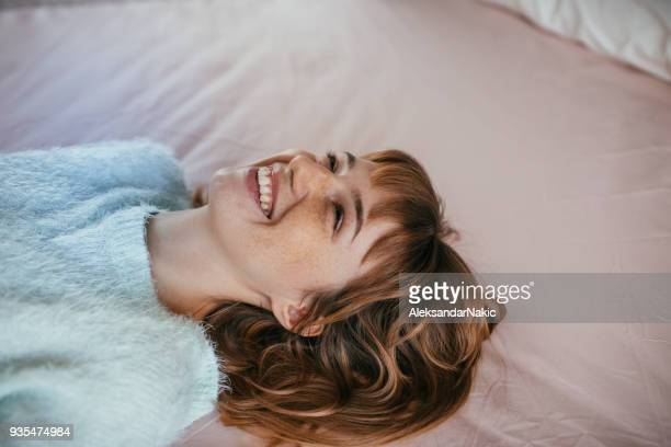 portrait of a smiling woman, lying on the bed - pastel stock pictures, royalty-free photos & images