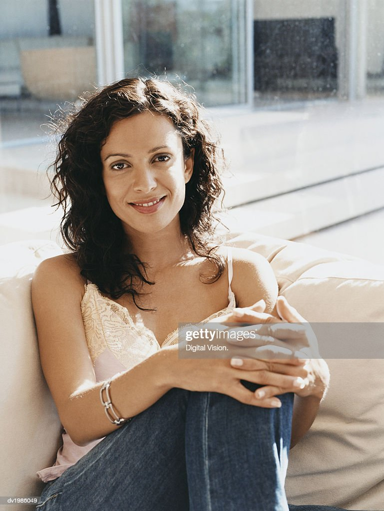 Portrait of a Smiling Woman Sitting on a Sofa : Stock Photo
