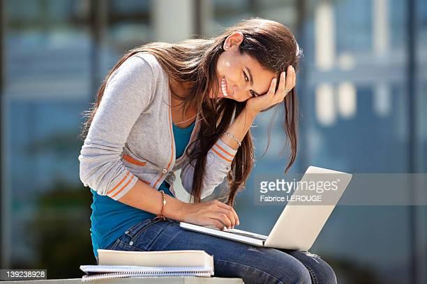 portrait of a smiling woman using a laptop - estudante universitária - fotografias e filmes do acervo