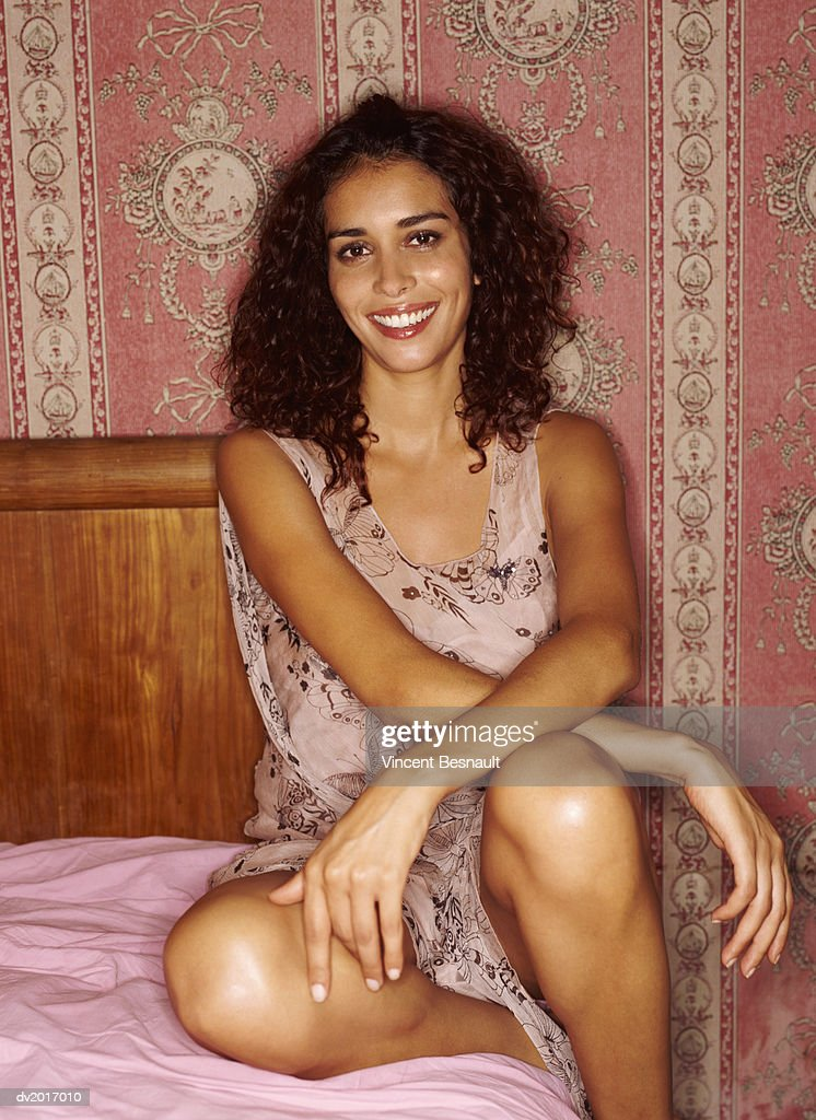 Portrait of a Smiling Woman with Curly Hair Sitting on a Bed : Stock Photo