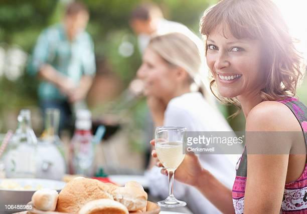 Porträt einer lächelnden Frau mit Menschen im Hintergrund