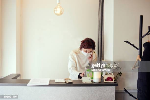 portrait of a smiling woman working using a phone or tablet at the front desk of an esthetic salon - store opening stock pictures, royalty-free photos & images