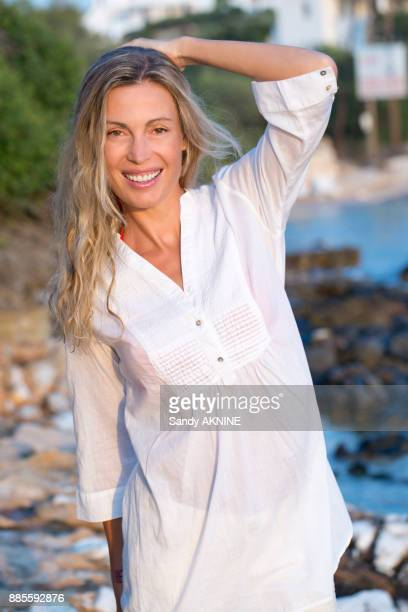 Portrait of a smiling young blonde woman in white shirt on the rock in the sea.